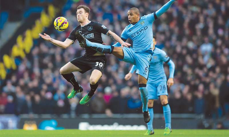 MANCHESTER: Burnley's Ashley Barnes (L) vies for an aerial ball with Manchester City's Fernando during their English Premier League match at the Etihad Stadium on Sunday.—AP