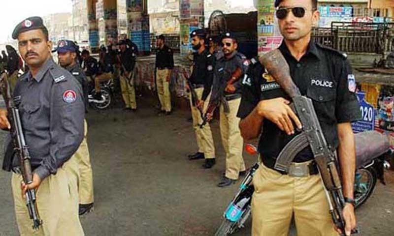 Policemen standing alert at a street in Karachi.—Online/File