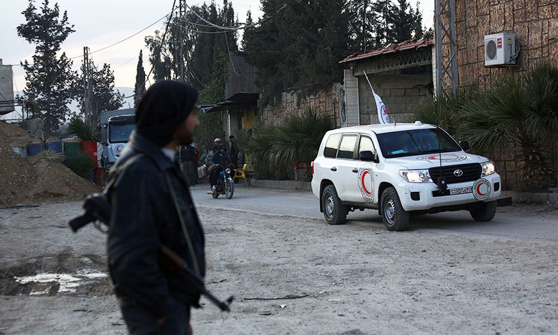 A rebel fighter looks on as trucks of vaccines are being brought in by members of the Syrian Arab Red Crescent to distribute in a rebel-held region outside the capital Damascus. -AFP Photo