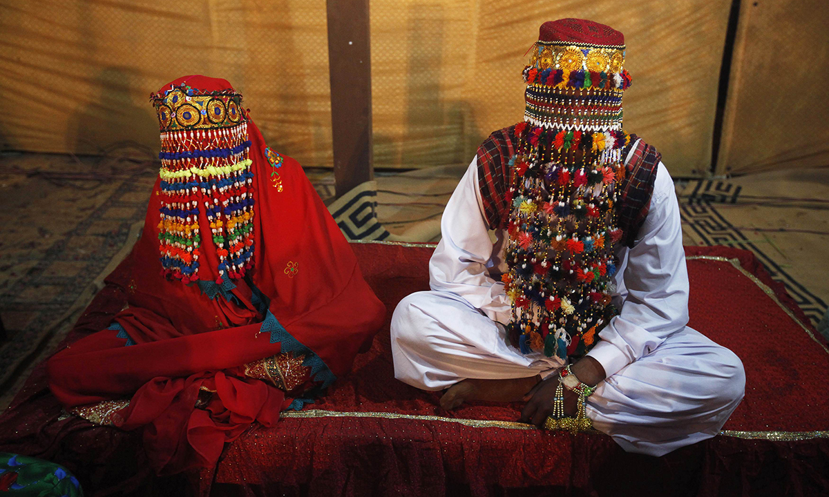 A bride and groom sit together during a mass marriage ceremony held in Karachi. — Reuters