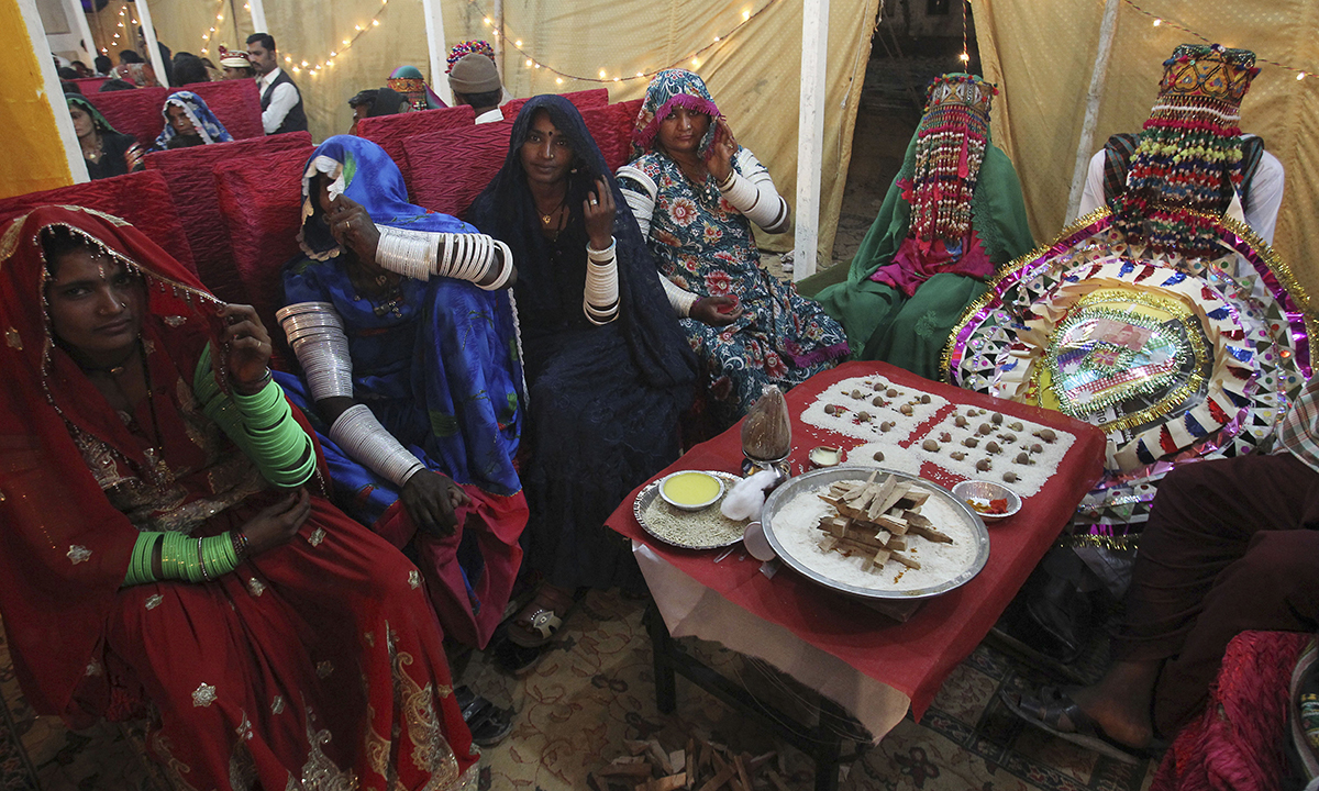 Hindu brides and a groom, far right, wait for a mass wedding ceremony. — AP