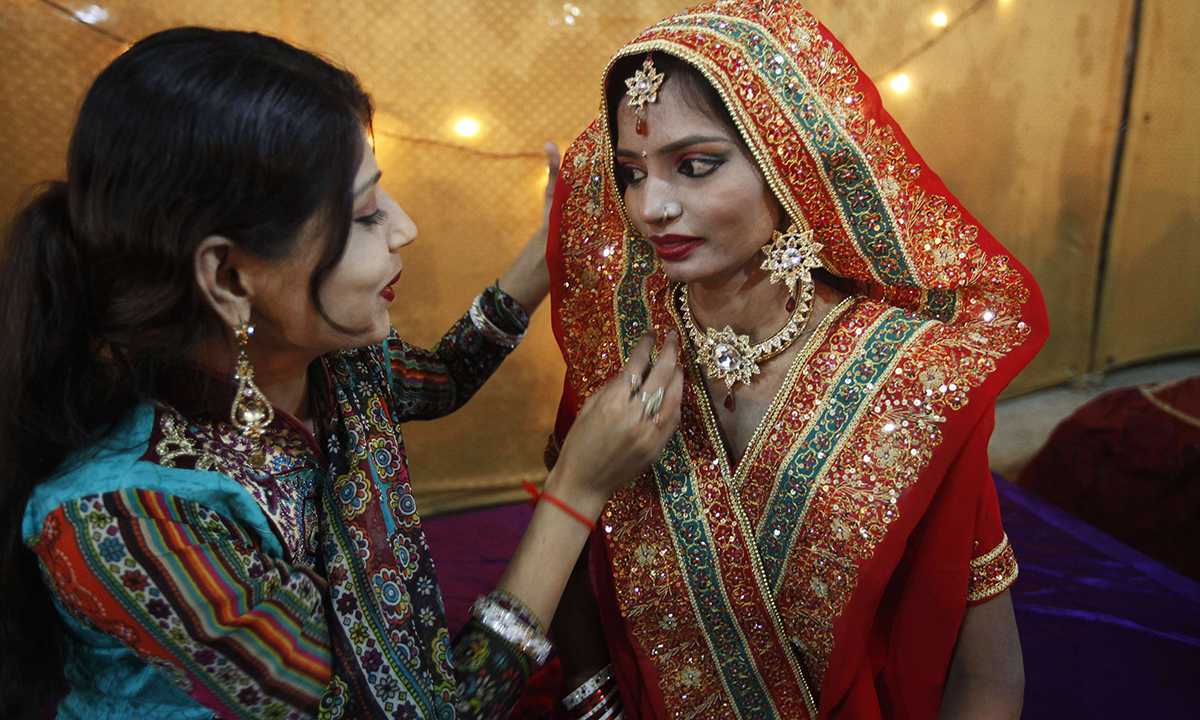 A family member adjusts the scarf of a bride. — Reuters