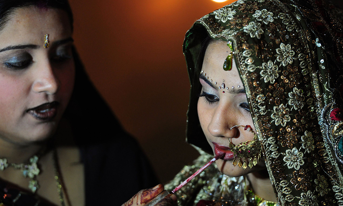A bride gets final touches from a relative. — AFP