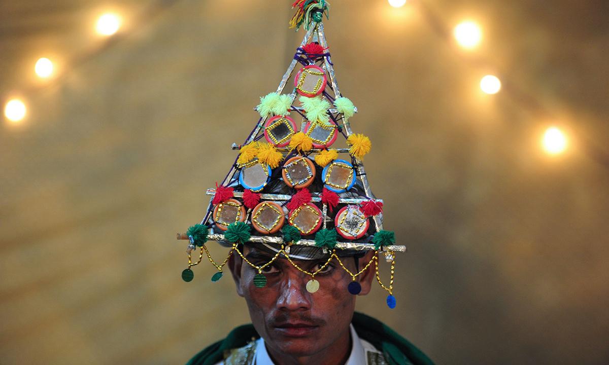 A Hindu groom wears a traditional cap. — AFP