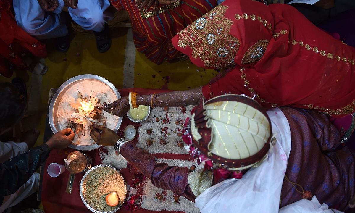 A  couple performs a Hindu rituals. — AFP