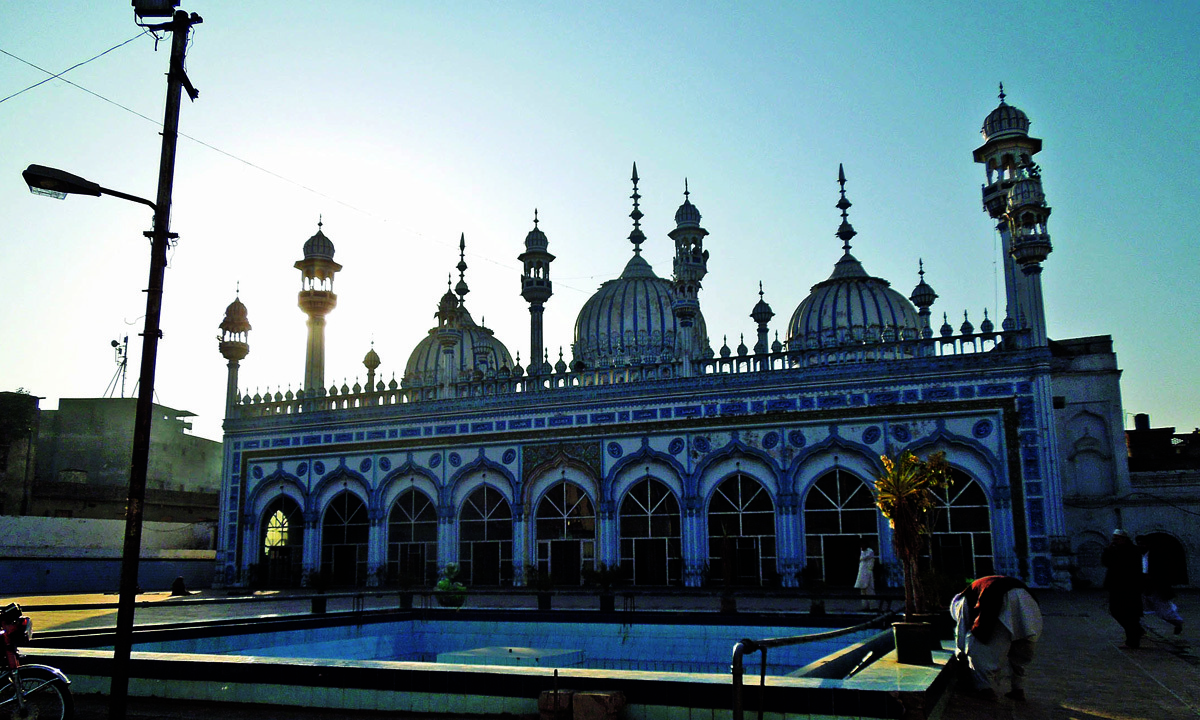 The main building of the mosque with three domes and several small minarets reflective of local aesthetic