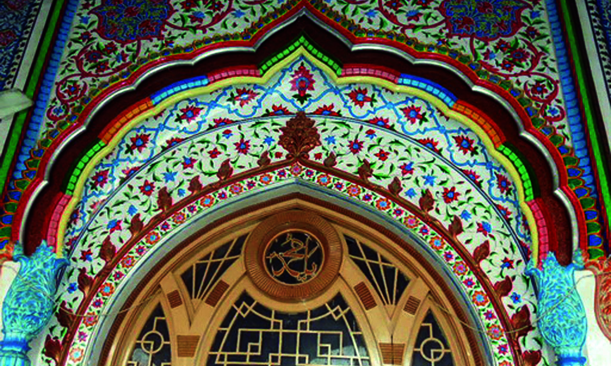 A colourful arch over a doorway divides three different patterns of fresco work