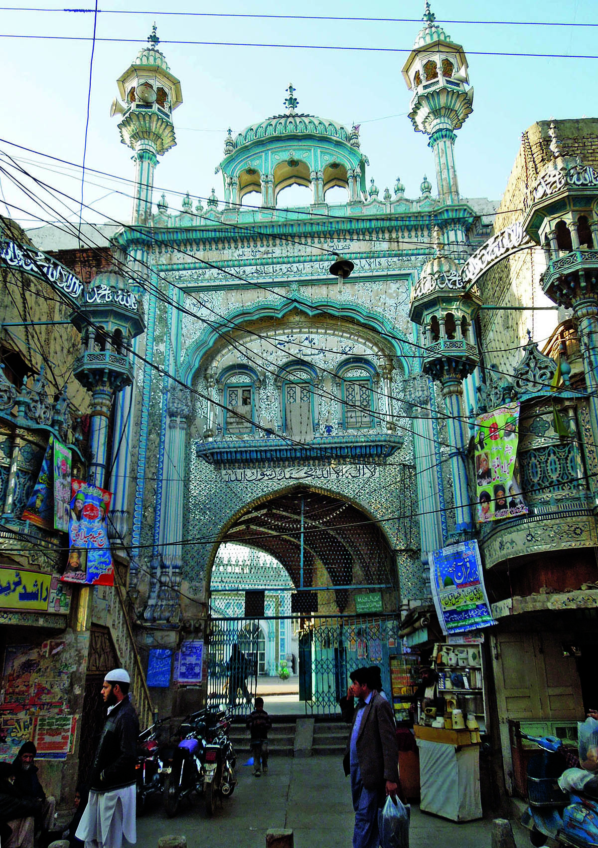The grand entrance of the Jamia Masjid with glass and paint work stands out from the clutter of modern hoardings and wires surrounding it