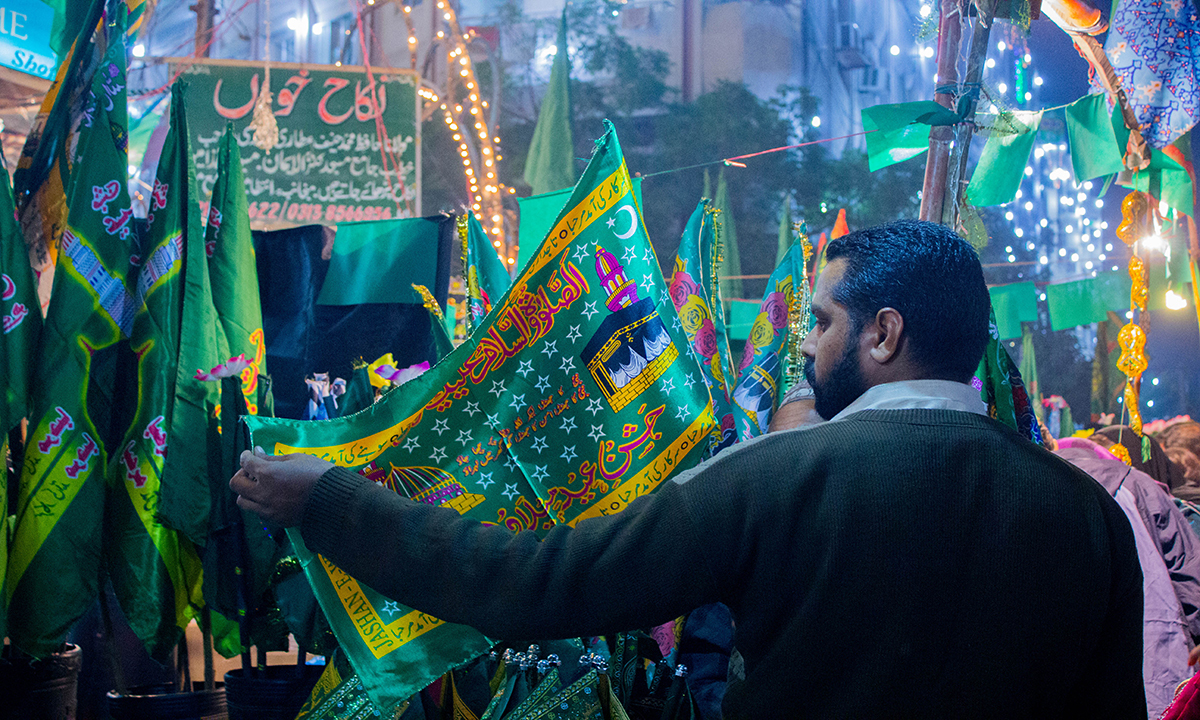 "A man selects one of the flags with "" Jashan e Eid Milaad un Nabi Mubarak"" (Celebrating birth of Prophet) written on it. — Muhammad Umar"
