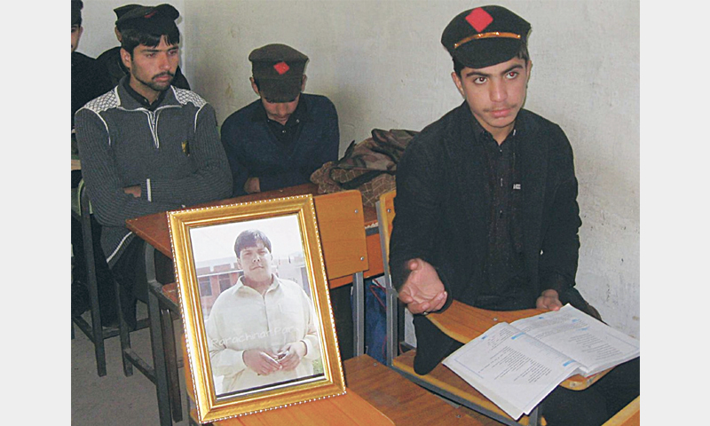 CLASSMATES of Aitzaz Hasan sit with his photo in Government High School, Ibrahimzai, now known as Aitzaz Hasan Shaheed High School.—AP