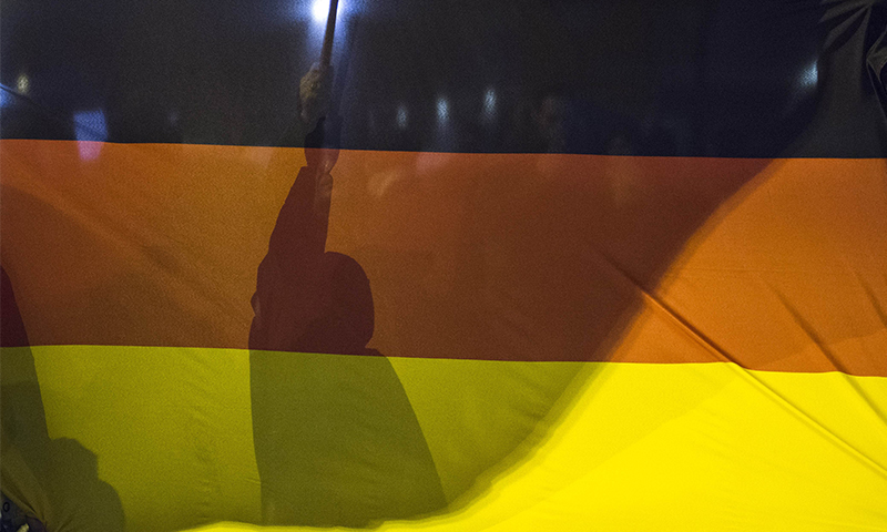 A demonstrator holds a flag behind a giant national flag during a rally by the mounting right-wing populist movement Pegida on January 5, 2015 in Berlin.--AFP