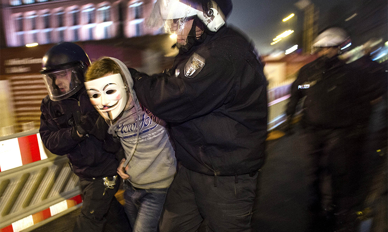 An anti-Pegida-protester wearing a Guy-Fawkes-mask is arrested by the police for refusing to leave the street during a demo against a rally by the mounting right-wing populist movement Pegida on January 5, 2015 in Berlin.--AFP