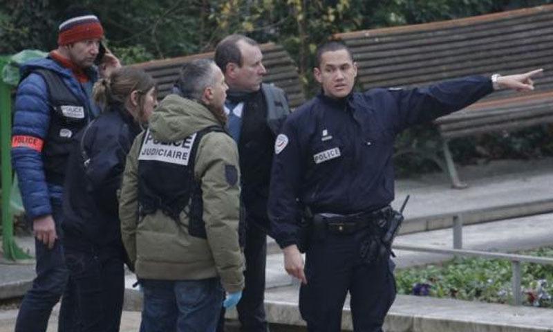ایک پولیس افسر فائرنگ کا نشانہ بننے والے رسالے کے دفتر کی طرف اشارہ کر رہا ہے—  رائٹرز فوٹو
