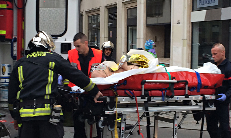 Firefighters carry an injured man on a stretcher in front of the offices of the French satirical newspaper Charlie Hebdo. - AFP Photo