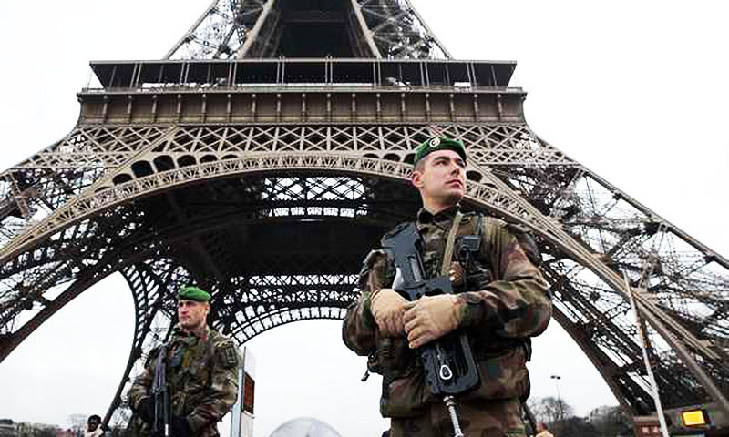 A French soldier stands guard in front of the Eiffel Tower as Paris is placed under the highest alert status. —AFP