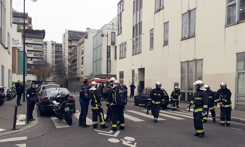 Police officers and firefighters gather in front of the offices of the French satirical newspaper Charlie Hebdo in Paris. —AFP/File