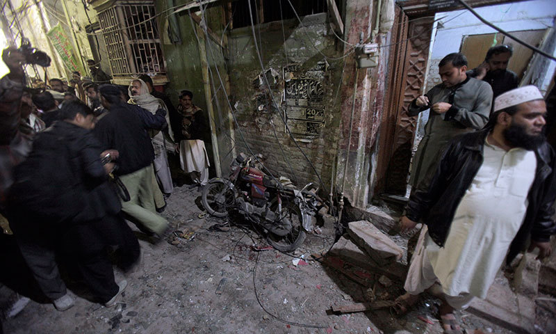 A police officer and local residents gather next to a damaged motorcycle at the site of a blast in Rawalpindi on Jan 9, 2015. – AP