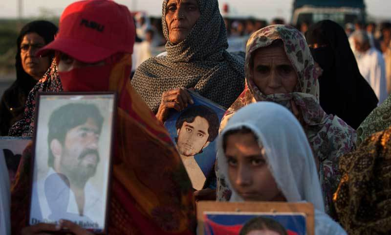 In this Nov 19, 2013, photo, people march towards Karachi holding photographs of their relatives who were allegedly abducted by security forces. — AP