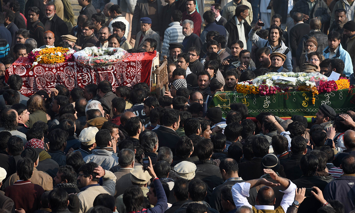 Coffins of victims are carried after funeral in Rawalpindi. — AFP