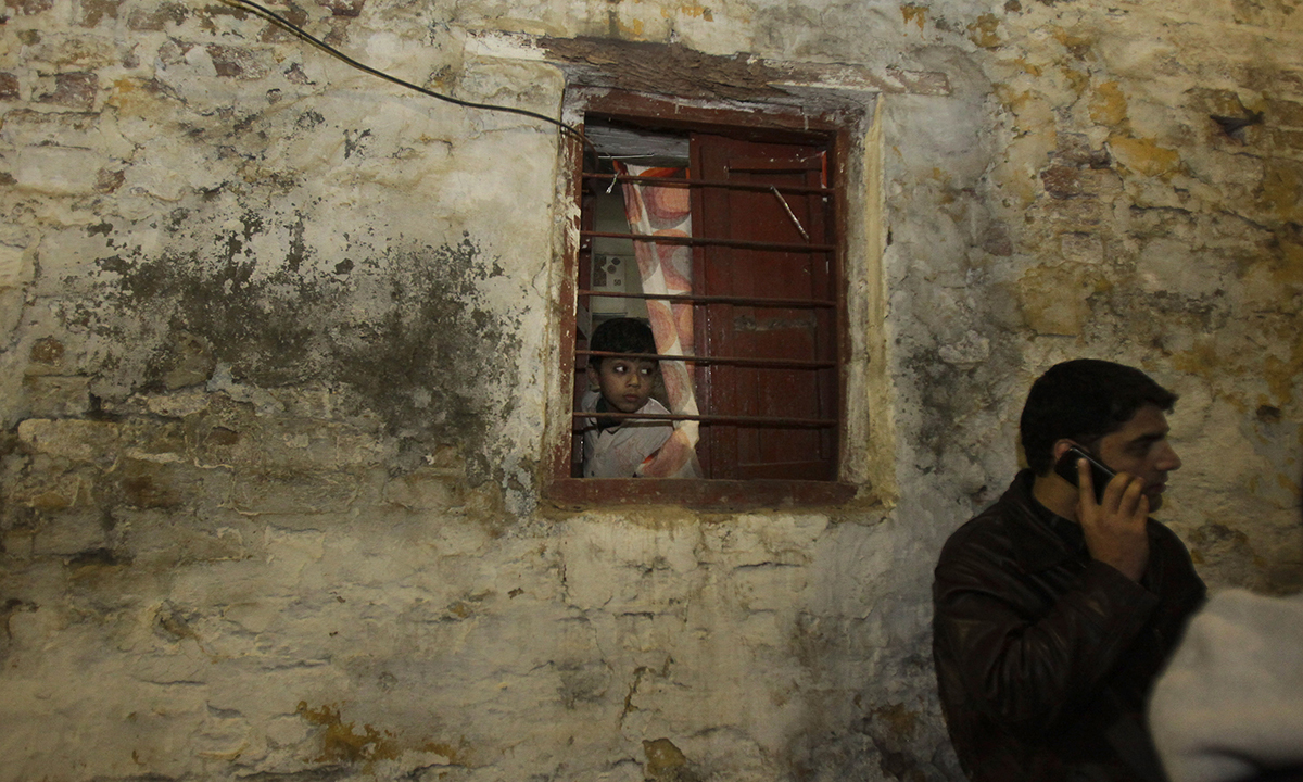 A boy looks out from the window of his house located near the blast site. — AP