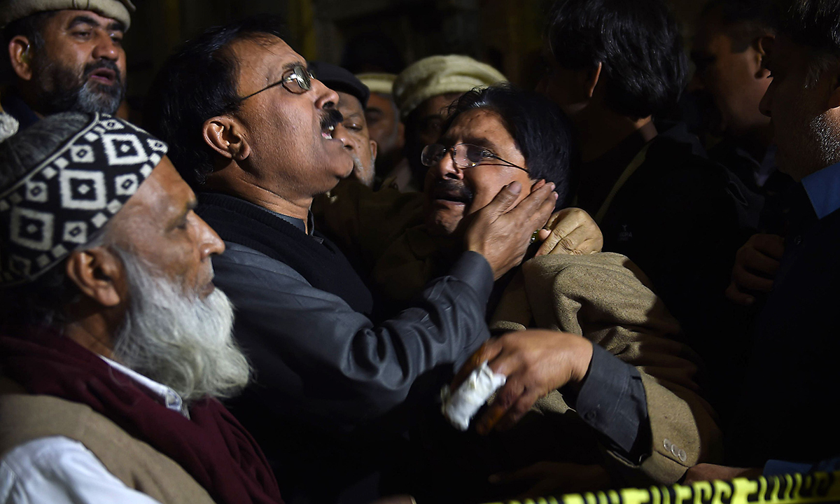 People mourn outside the site of a blast in Rawalpindi. — AFP