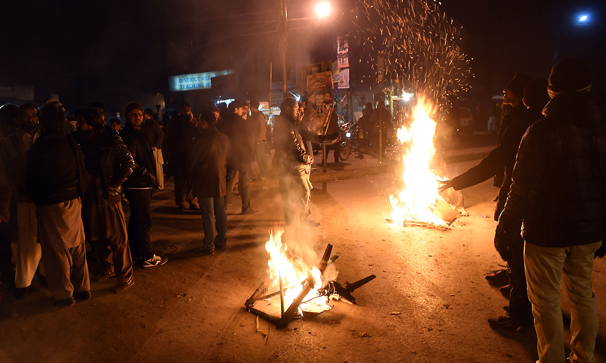 People burn wood outside a hospital where victims were being treated after a blast in Rawalpindi. — AFP