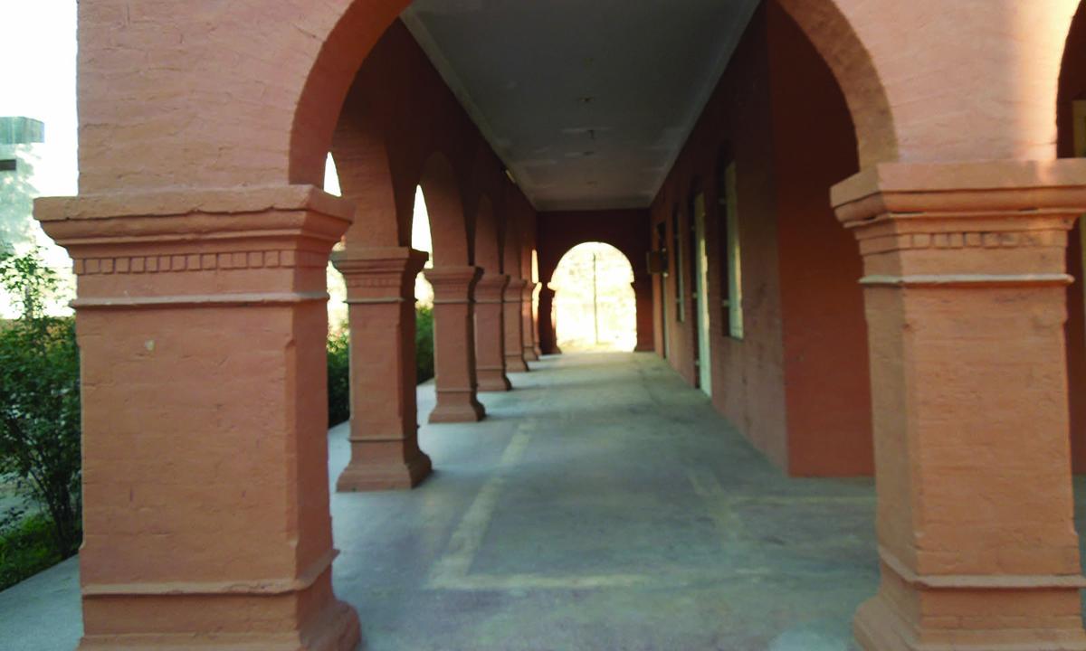 The long verandah of the building, seen through an arch.