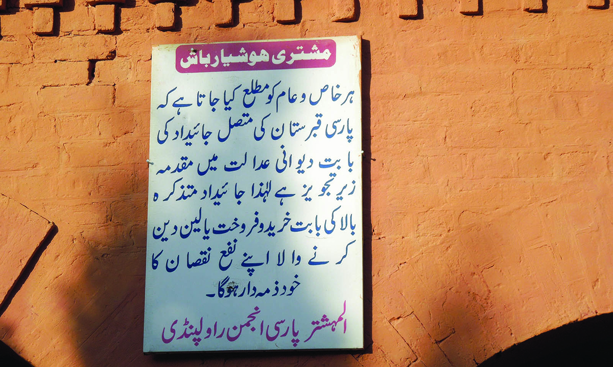 A notice in Urdu on the building, warning people against getting into transactions of this property which is awaiting litigation in court.