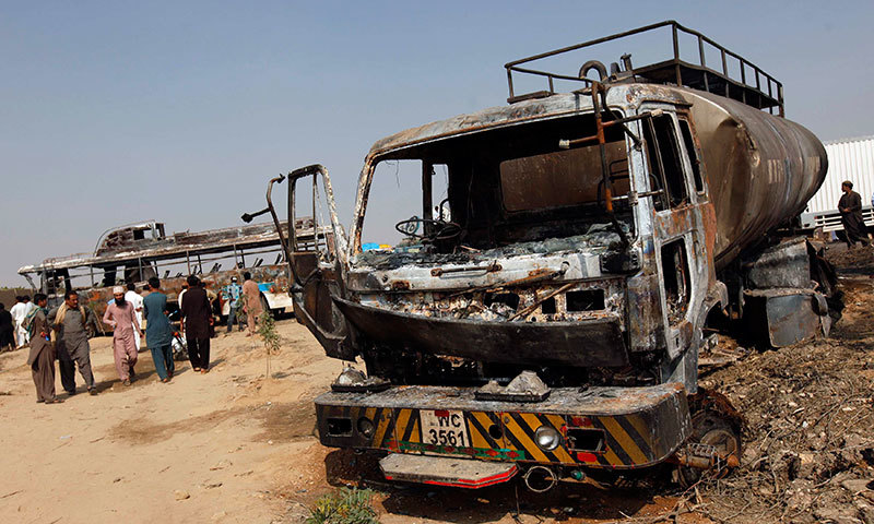 People look at the wreckage of a bus and tanker after they collided early Sunday, on the outskirts of Karachi. -Reuters Photo