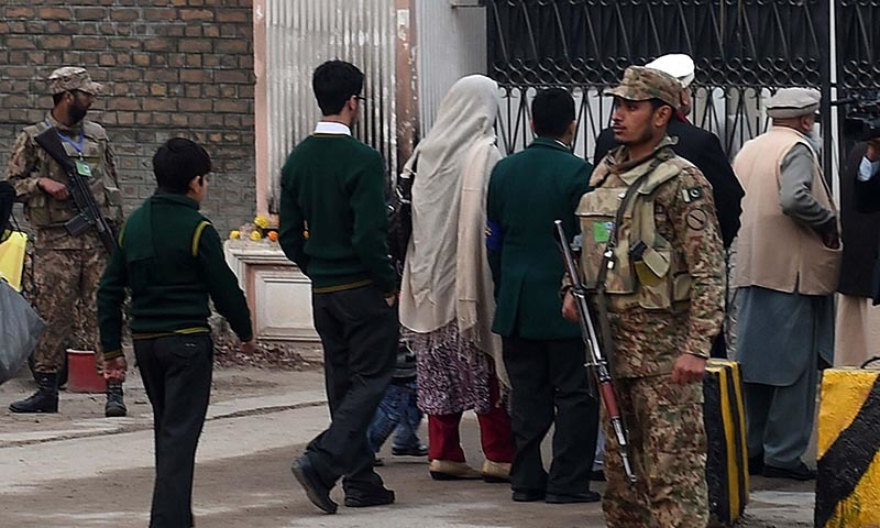 Soldiers stand guard as children arrive with their parents at the Army Public School in Peshawar on January 12, 2015. — AFP