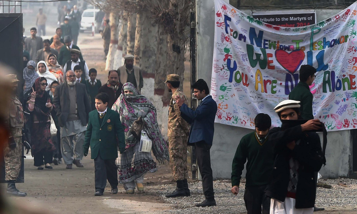 Parents leave the school with their children after it was reopened. — AFP