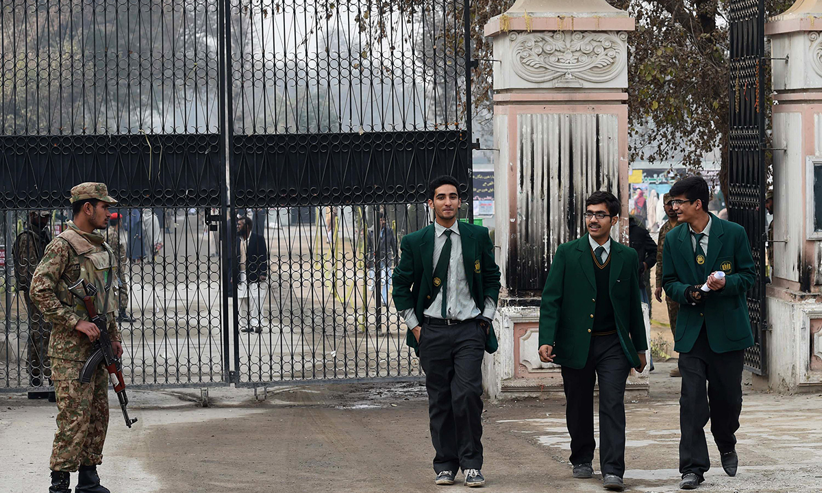 Pakistani soldiers stand guard as students leave. — AFP