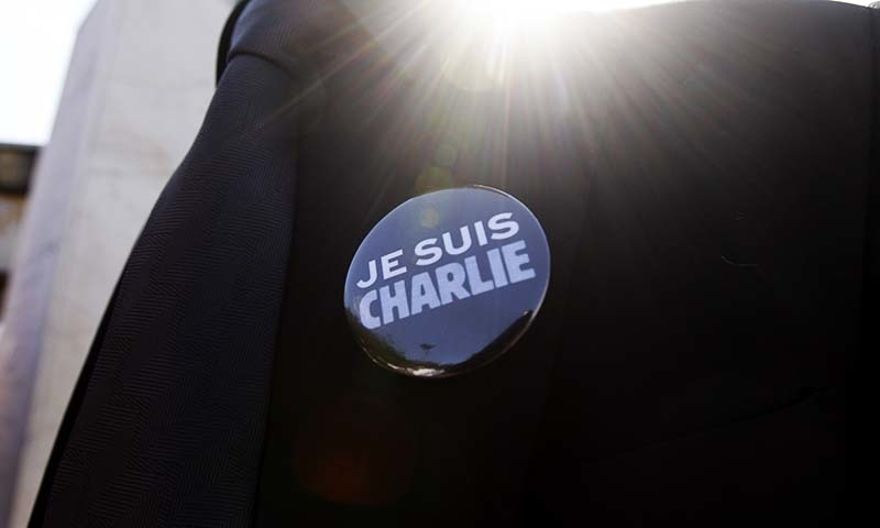 """A man in suit wears a """"Je Suis Charlie"""" (I am Charlie) button, during a gathering in solidarity with victims of the recent Paris terrorist attacks, at the Plaza de Francia in Panama City, Jan 12, 2015. — AP"""