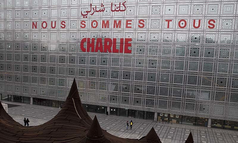 """A slogan reading """"Nous sommes tous Charlie"""" (We are all Charlie) in Arabic and French has been put on the facade of the Institute of the Arab World (Institut du Monde Arabe, IMA in French) in Paris, on January 12, 2015. — AFP"""