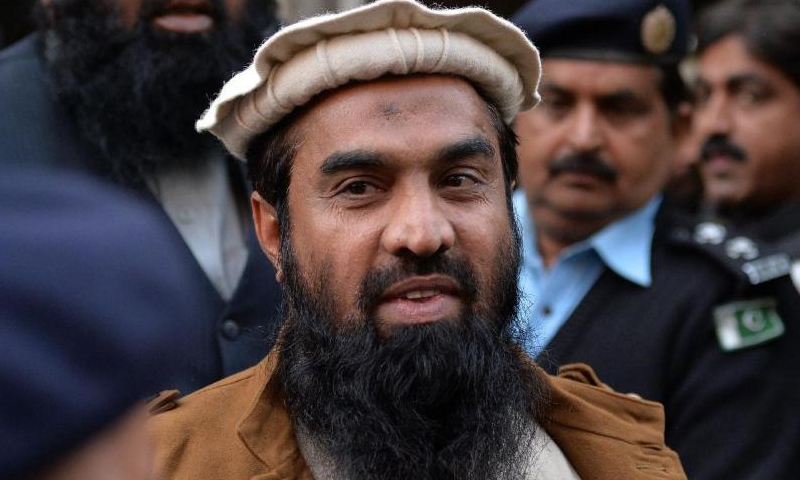 Security personnel escort Zaki-ur-Rehman Lakhvi from a courthouse after a hearing in Islamabad, on January 1, 2015.— AFP/File