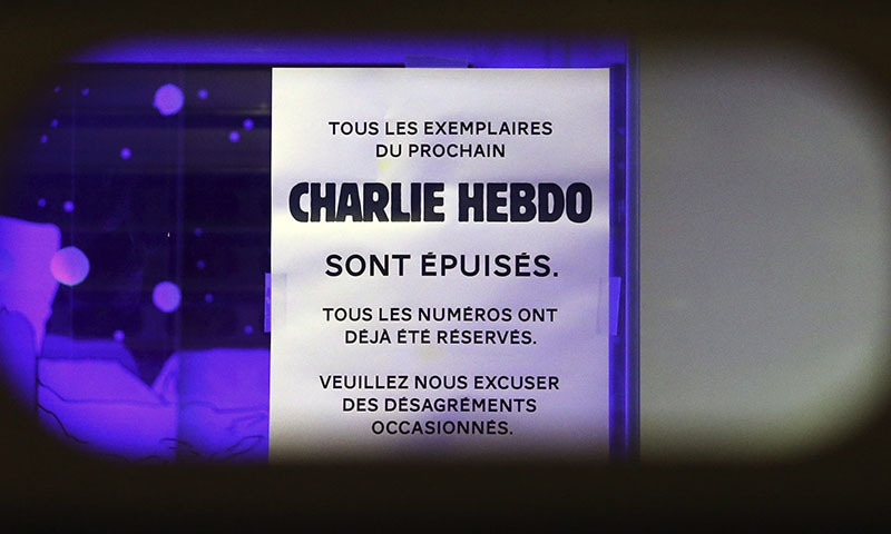 """A sign that reads """"All copies of the next Charlie Hebdo have been sold out. All copies have already been reserved. Please excuse the inconvenience caused,"""" is displayed in a bookstore in Brussels."""
