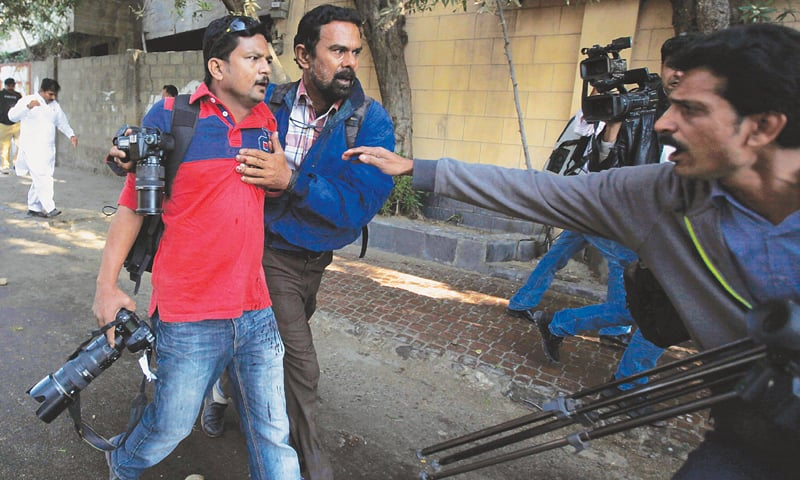 Asif Hassan, a photojournalist of the Agence France-Presse, is being helped by a cameraman after he was shot in the chest during a protest held by the Islami Jamiat-i-Talaba near the French consulate on Friday.—Reuters