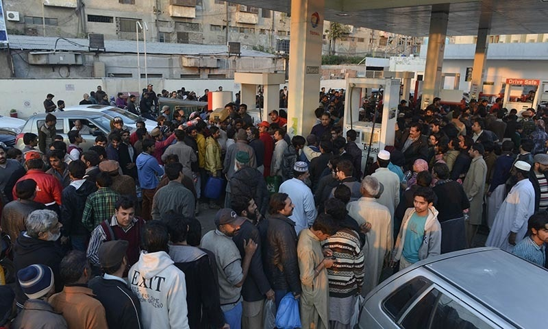 Motorists queue at a petrol station in Lahore on January 17, 2015. — AFP