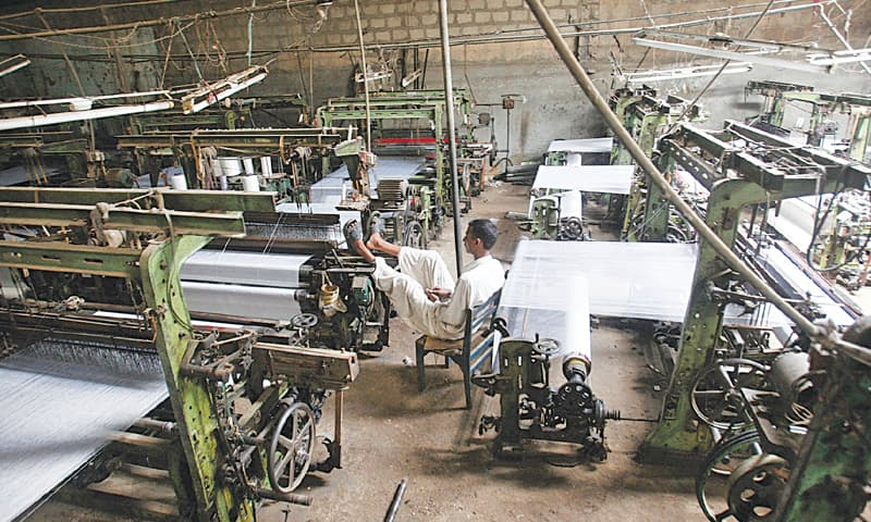 """A man sits inside a closed power loom unit. Aptma chairman S.M. Tanveer says """"We can revive our closed capacity of $3-4bn, attract investment of over $5bn in capacity expansion and value-addition, and double our textile and clothing exports to $26bn in five years if the government ensures uninterrupted electricity supply to factories in Punjab at regionally affordable prices"""". —Reuters/File"""