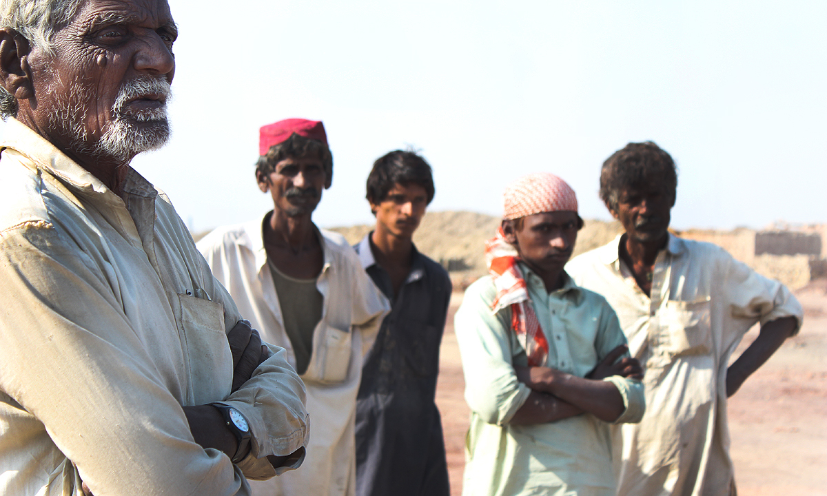 Men at a brick kiln gather to speak of their woes.