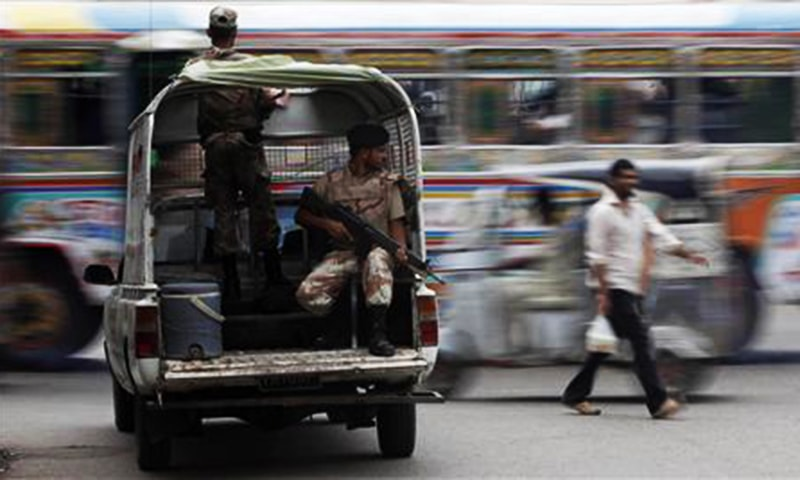A man walks past a moving bus as Rangers keep guard at an intersection in Karachi. — Reuters/file