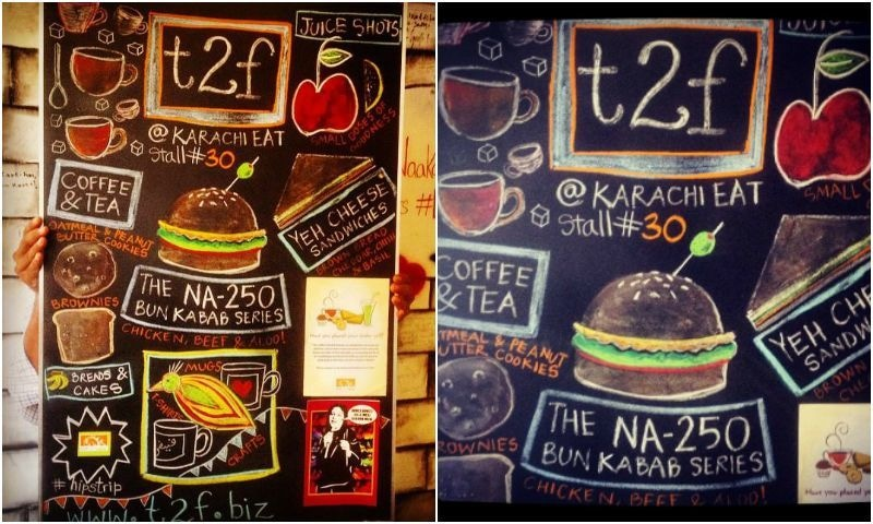 A member of T2F's team holds up a blackboard displaying the menu for the upcoming festival. Find T2F at Stall No. 30A - Photo courtesy: Raania Durrani