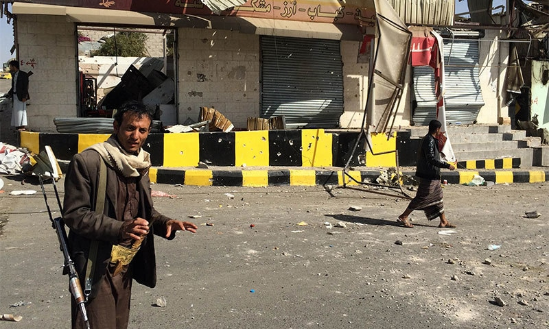 An armed member of the Huthi movement stands guard in a damaged area following clashes the previous day near the presidential palace in the capital Sanaa. -AFP Photo