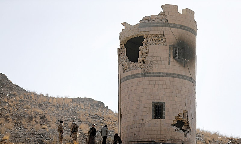 Huthi fighters stand near a damaged post at a Presidential Guards barracks on a mountain overlooking the Presidential Palace they seized on Tuesday. — Reuters