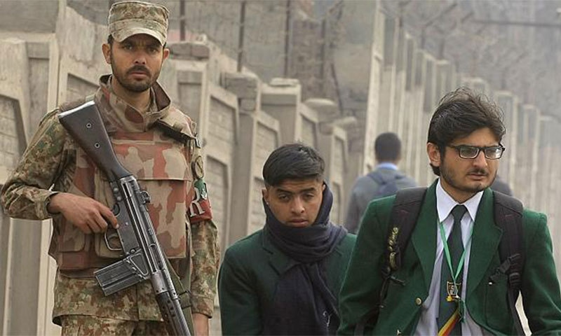 Students walk to school as a soldier stands guard outside the Army Public School which was targeted by Taliban militants in December. -AP Photo