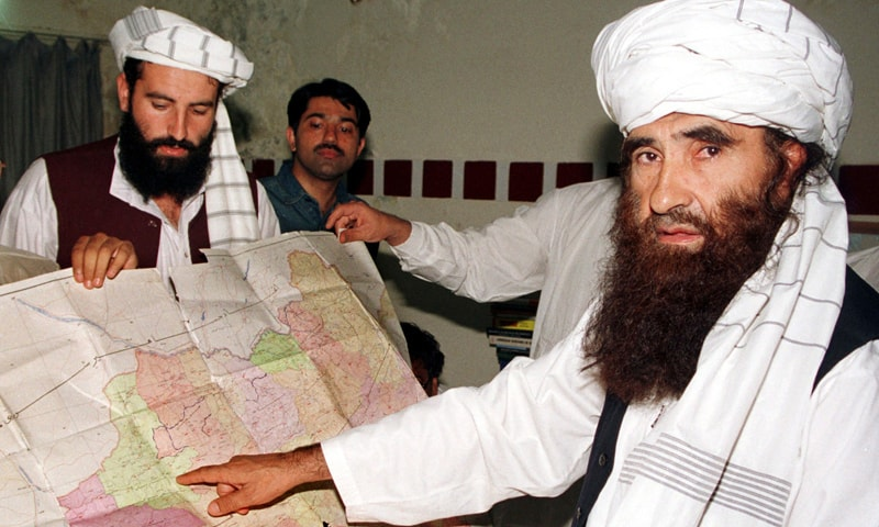 Jalaluddin Haqqani (R), Taliban's Minister for Tribal Affairs, points to a map of Afghanistan as his son Nasiruddin (L) looks on during a visit to Islamabad, in this file picture taken October 19, 2001. —Reuters