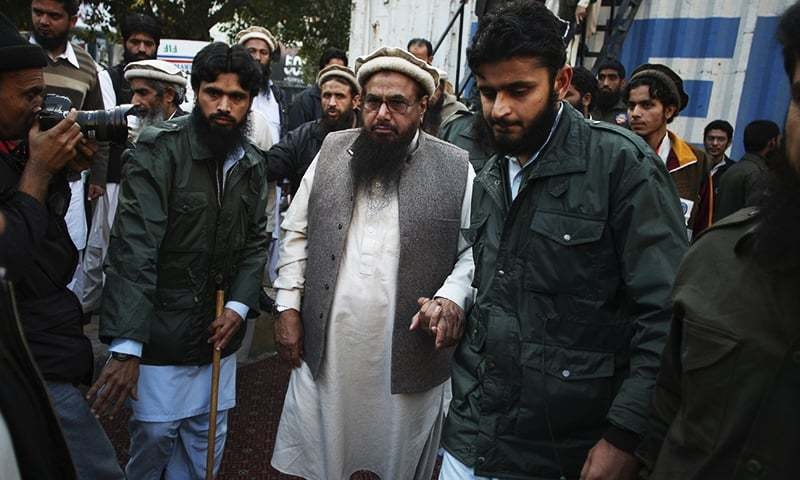 Hafiz Saeed, center, head of religious group Jamaat-ud-Dawa leaves after addressing a rally against caricatures published in French magazine Charlie Hebdo, in Lahore, Pakistan, Sunday, Jan. 18, 2015. -AP/File