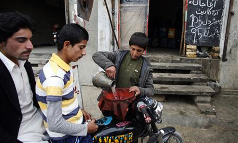 A boy fills the tank of a motorbike with smuggled petrol along a roadside shop in Quetta February 13, 2013.— Reuters/file