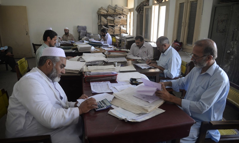 Men work amidst stacks of files at the Pesco office in Peshawar | Shahbaz Butt, White Star
