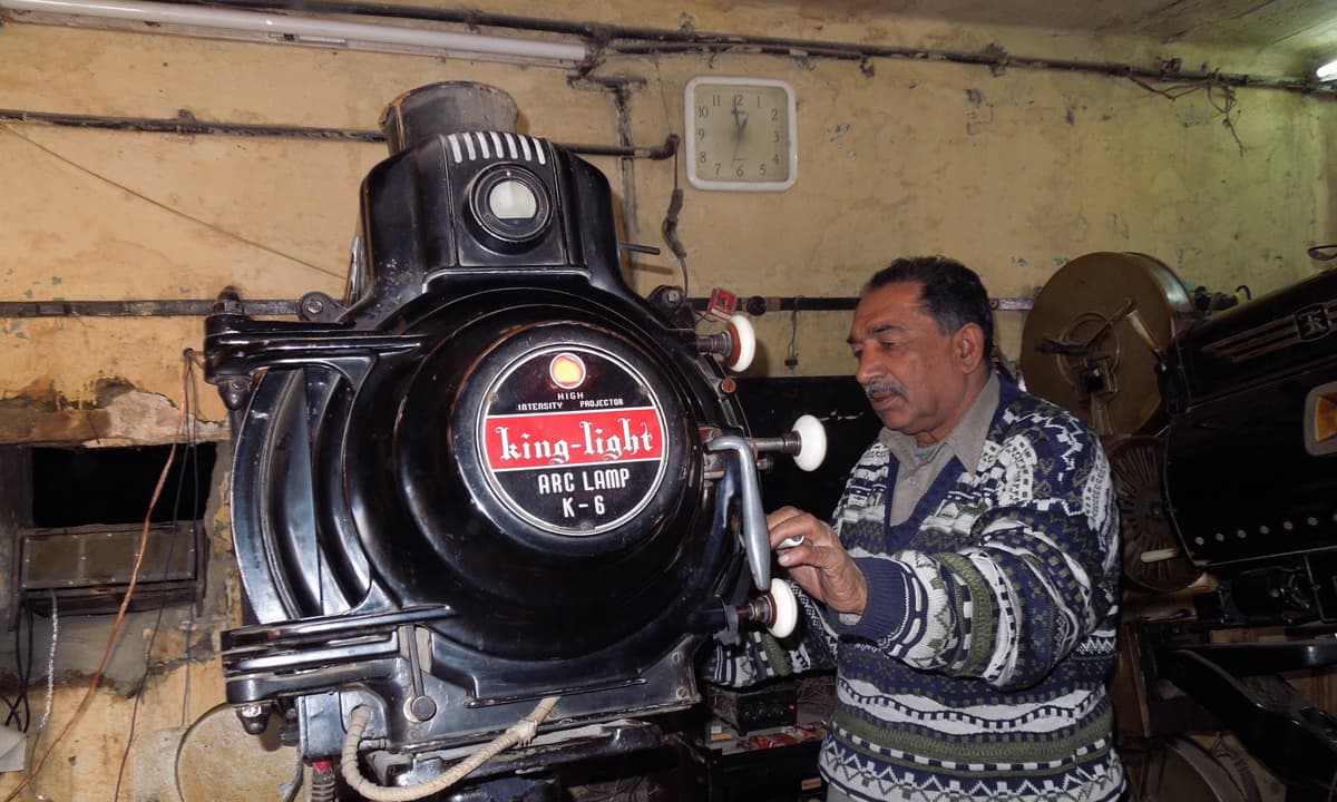 Projectionist Asghar Ali Butt operates the old movie projector during a film screening. — Photo by Shiraz Hassan